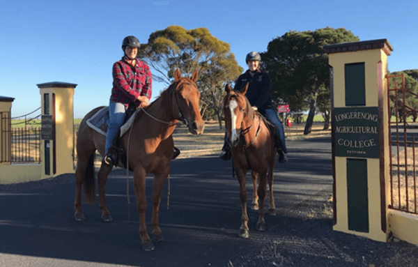 Students on horses in front of Longy gates