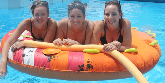 Students in pool on floating tube