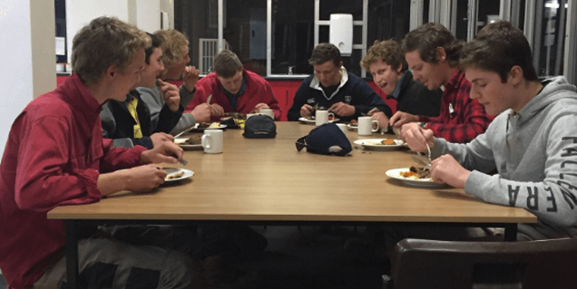 Group of students eating lunch at table in College cafeteria