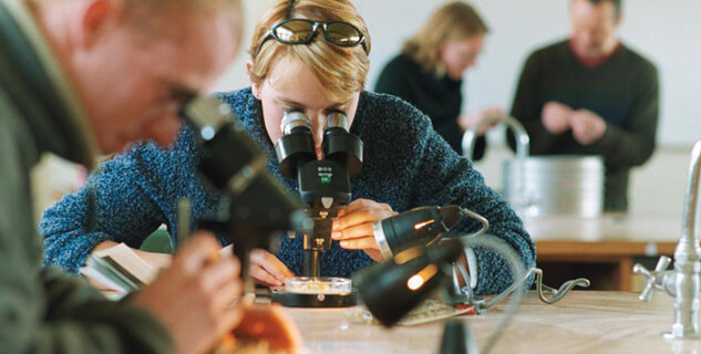 Longy College student looking into microscope