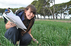 Agronomy student on Longy College farm with school books